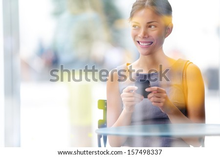 City lifestyle business woman using smartphone on cafe. Young professional female businesswoman on smart phone while sitting indoors in cafe looking out. Multicultural Asian Caucasian girl in her 20s. - stock photo
