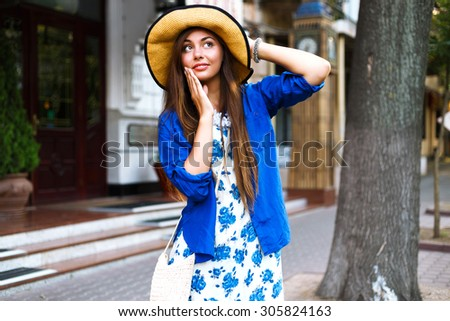 City lifestyle fashion portrait of happy pretty girl walking alone having fun on the street, evening sunlight, retro dress vintage hat, happy positive mood.  - stock photo
