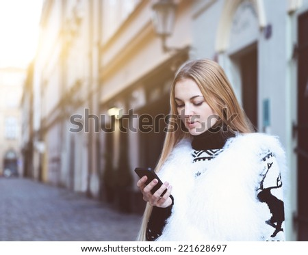 City lifestyle. Stylish woman using a phone texting on smartphone in a street in winter time - stock photo