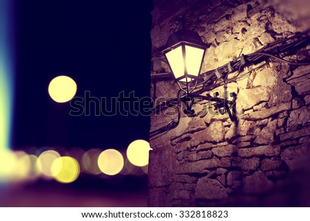 City lights and lamppost in the facade.Stone wall background at night - stock photo