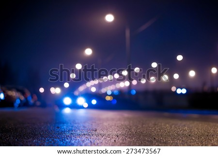 City night lights, road bridge with the lights and moving car in the fog after rain. View from the level of asphalt, in blue tones - stock photo