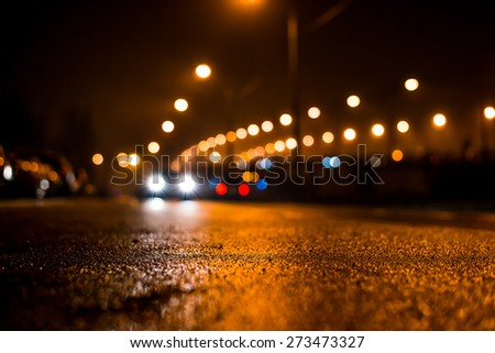 City night lights, road bridge with the lights and moving cars in the fog after rain. View from the level of asphalt - stock photo