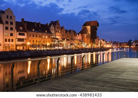 City of Gdansk in Poland by night, Old Town skyline, boardwalk promenade at Motlawa River - stock photo