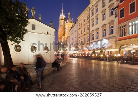 City of Krakow by night in Poland. Main Square in the Old Town, Church of St. Wojciech on the left, tenement houses and St Mary Basilica at the far end. - stock photo