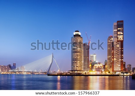 City of Rotterdam downtown skyline at dusk in South Holland, Netherlands, Erasmus Bridge on the left. - stock photo