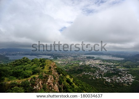 city of Udaipur, Rajasthan, India, seen from Monsoon Palace, on the top of the mountain. the palace has been built in 1884, Mewar Dynasty, basically for watching the monsoon clouds. - stock photo