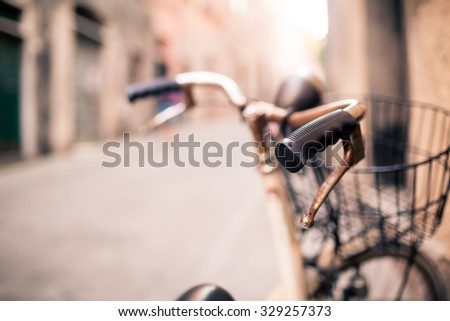 City old bicycle handlebar and basket over blurred beautiful bokeh background on Europe city street. Vintage retro style bike with bokeh copy space. Selective focus on handlebar. - stock photo