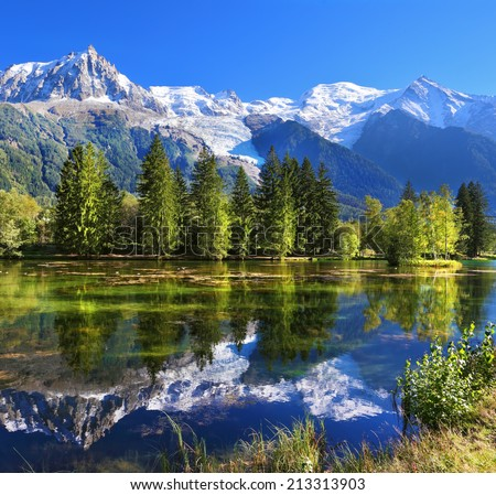 City park in the mountain resort of Chamonix in France. Snowy mountains and evergreen spruce reflected in the lake - stock photo