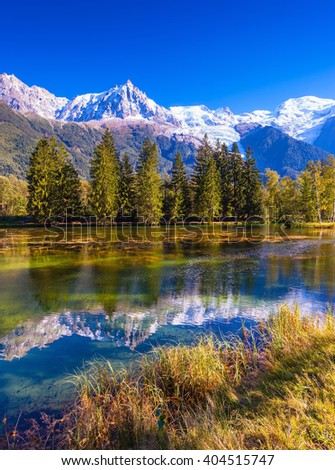 City Park is illuminated by the setting sun. The lake reflected the snow-capped Alps. The mountain resort of Chamonix,  France - stock photo