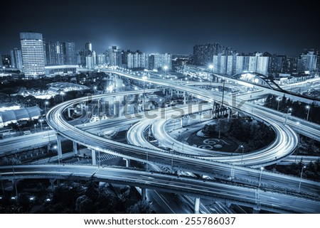 city road junction at night ,interchange highway with blue tone - stock photo