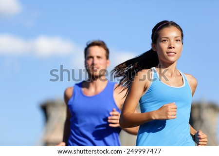 City running couple jogging outside. Runners training outdoors working out in Brooklyn with Manhattan, New York City in the background. Fit multiracial fitness couple, Asian woman, Caucasian man. - stock photo