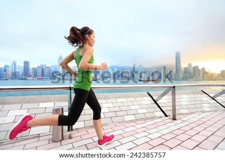 City Running - woman runner and Hong Kong skyline. Female athlete fitness athlete jogging training living healthy lifestyle on Tsim Sha Tsui Promenade and Avenue of Stars in Victoria Harbour, Kowloon. - stock photo