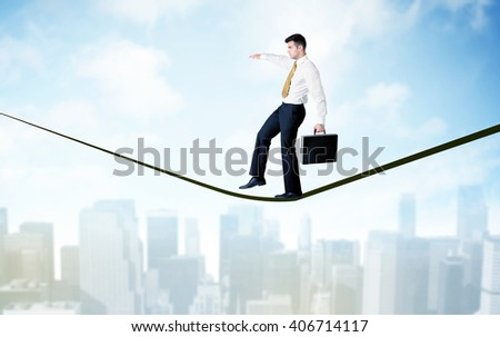 City scape, tall buildings and clouds on clear blue sky with business person balancing on black rope concept - stock photo