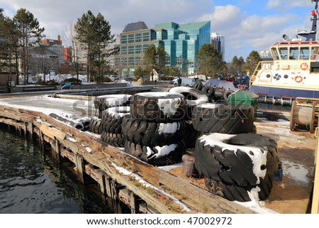 city seen from a wharf stacked with tractor tires - stock photo