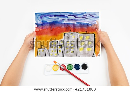 city skyline at sunset, skyscraper with light in window, home silhouette on dark sky background, child drawing, top view hands with pencil painting picture on paper, artwork workplace - stock photo