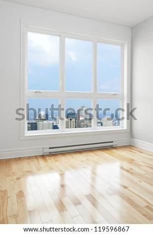 City skyscrapers seen through the big window of an empty room. - stock photo