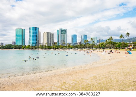 City skyscrapers view next to the golden beach of Waikiki, Hawaii. - stock photo
