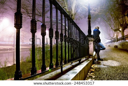City street at night with trees,man and lamppost - stock photo