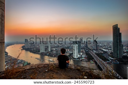 City town at sunset, Bird eyes view, Bangkok, Thailand,one person sit at edge of building - stock photo