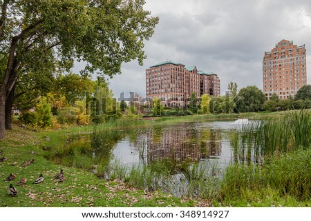 City townhouse and block buildings neighborhood with a lot of trees, park and lake nearby. Autumn weather, clouds. - stock photo