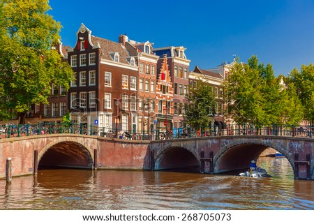 City view of Amsterdam canal, bridge and typical houses, boat and bicycles, Holland, Netherlands.  - stock photo