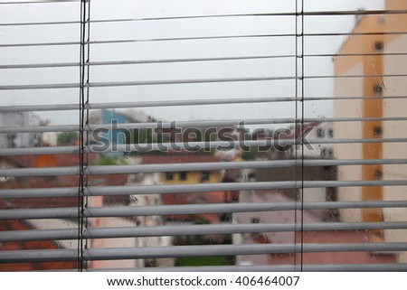 City view through a window on a rainy day. rain through window blinds - stock photo