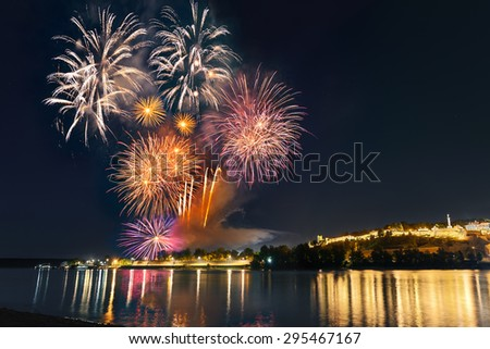 Cityscape and colorful multiple fireworks at the foot of the famous tourist landmark Kalemegdan fortress at night, with reflection on river Sava. Belgrade - Serbia. - stock photo