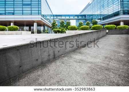 cityscape and empty concrete footpath by modern building in cloudy sky - stock photo