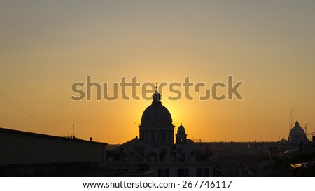 Cityscape in Rome at dusk with sun back the cupola - stock photo
