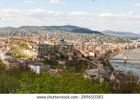 Cityscape of Budapest in warm sunlight with Buda Castle visible through trees of Gellert Hill. - stock photo