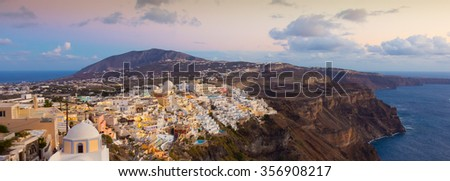 Cityscape of Fira, dramatically located on the edge of the caldera cliff on the island of Thira known as Santorini, Greece. Panorama shot at dusk. - stock photo