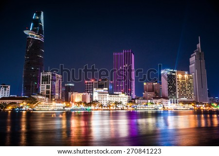 Cityscape of Ho Chi Minh at night with bright illumination of modern architecture, viewed over Saigon river in Southern Vietnam. - stock photo