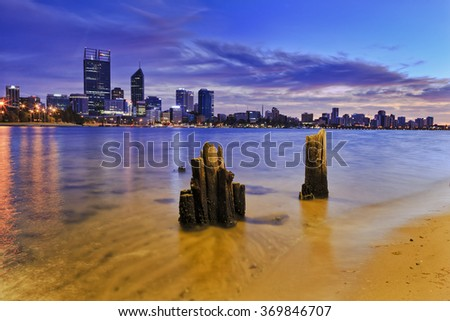 cityscape of Perth - capital city of Western Australia at sunrise; Fragments of jetty in forefront standing out from clear swan river sand - stock photo