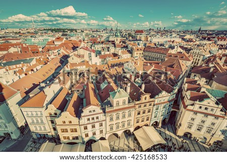 Cityscape of Prague, Czech Republic. View on traditional red roof tenement houses as seen from Old Town City Hall. Blue sunny sky, wide angle skyline. Vintage - stock photo