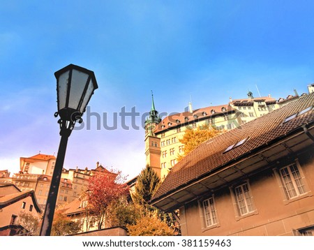 Cityscape of the old town in Fribourg, Switzerland, including a traditional street light, numerous houses and the city hall in background - stock photo