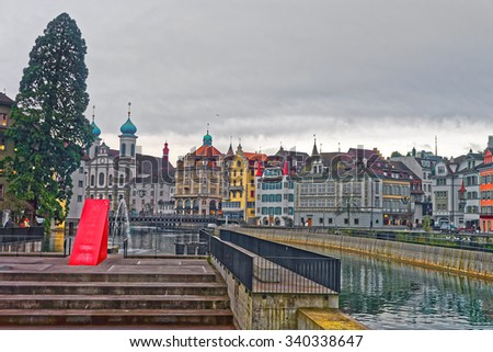 Cityscape of the swiss city of Lucerne with ornate Jesuit Church, located on the railway station side of the River Reuss, and beautiful medieval buildings. - stock photo