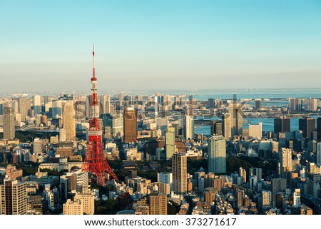 Cityscape of Tokyo at dusk, as seen from the top of one of the highest buildings in Roppongi Hills, with the red and white Tokyo Tower rising over other buildings. - stock photo