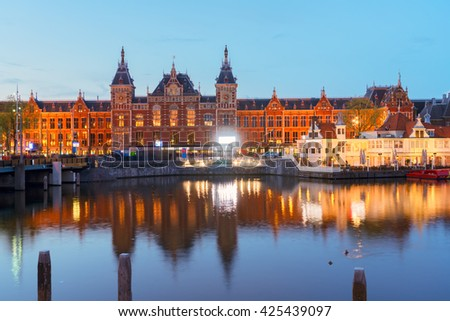 cityscape with central railway station and old town canal illuminated at night, Amsterdam, Holland - stock photo