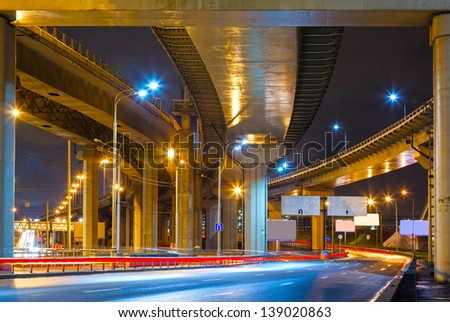 cityscape with road overpass in the lamplight with reflections on the asphalt - stock photo
