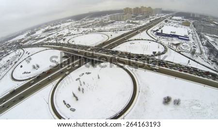 Cityscape with traffic on interchange of belt way at winter day during snowfall. Aerial view - stock photo