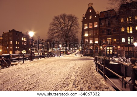 Cityscenic from Amsterdam covered with snow in the Netherlands at night - stock photo