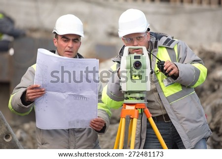 Civil Engineer and Surveyor at at construction site are inspecting ongoing production according to design drawings. - stock photo