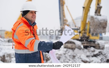 Civil engineer at construction site is inspecting ongoing works according to design drawings in difficult winter conditions - stock photo