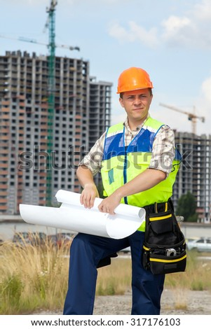 Civil engineer wearing a safety vest with a plan on construction site. Belt with the tools on his belt. - stock photo