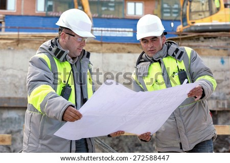 Civil Engineers at at construction site are inspecting ongoing production according to design drawings. - stock photo