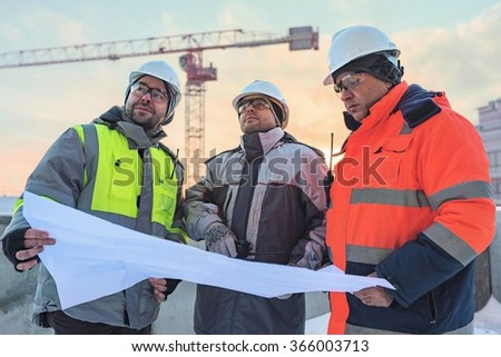 Civil Engineers at construction site are inspecting ongoing production according to design drawings. - stock photo