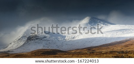 Clach Leathad hidden in cloud with the summit of Meall a Bhuiridh just clear of clouds for a few minutes on a winter day Viewed from Rannoch Moor - stock photo