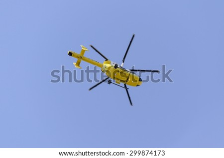 Clacton-on-sea, Essex, England, UK: 1 August 2013- Helicopter rescue, Yellow helicopter in the air while flying in a  blue sky, on its way to rescue someone. - stock photo