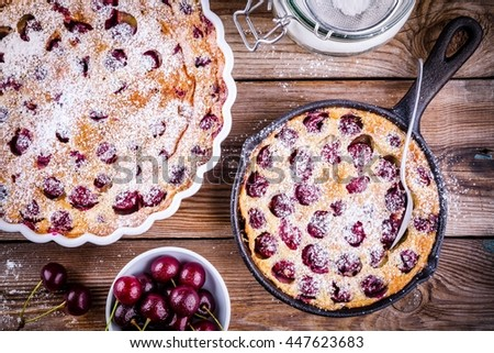 Clafoutis cherry pie on rustic wooden background - stock photo