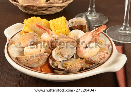 Clams, corn on the cob, shrimp and mussels in herbed garlic lemon butter sauce - stock photo